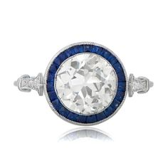A stunning Old Euro Cut diamond Estate Engagement Ring surrounded by a halo of Sapphires. The diamond is approximately 2.24ct, L color and VS1 clarity.