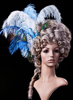 €212,00 EUR; Hair color: grey-blond. Ornament color: variations of blue and white. Lady's wig extravagantly adorned with decorative feathers, a butterfly as well as Swarovsi rhinestones.