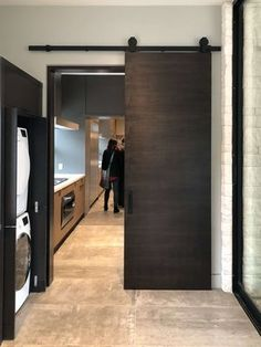 Contemporary tall wood barn door closes off the laundry room when needed in The New American Remodel Wood Barn Door, Barn Doors, Light Paint Colors, Craftsman Style Doors, Dark Wood Stain, Small Hallways, Spacious Living Room, Beautiful Bedrooms, White Trim