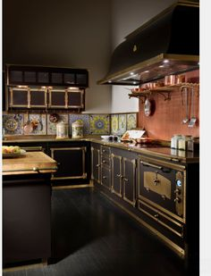 French… but what I like is the brass towel bar on the side of the butcher block topped island… just on the left;