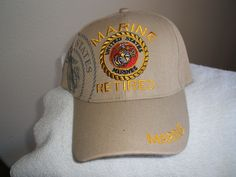 U S Marine Corps (Retired) emblem on a new Tan ballcap or cover: US Marine Corps (Retired) new tan ballcap with the shadow USMC emblem on the side and front and Marine on the bill. It has a velchro strap on the ball of for adjustment. Only one tan left..see my yardsale for more caps....