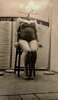 Curiosa, a popular sideshow gaff where a woman sits behind a light board fitted over her shoulders so it appears as her headless body powers a lightbulb  ca. 1920