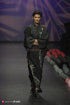 kimononagoya:  One of the Men's Kimono from the Saitou show, this Dark black and grey kimono features what looks like a Botan {Peony}. Traditionally some flower motifs were considered more masculine than others, with the Botan being a particularly boyish one. Although it is now a popular spring flower to feature on women's Kimono, much of that is because of the strength and vitality associated with the flower.Probably also because it's pretty.In any case we have it here decorating the men's Kimono in the standard (booooring) greys, however because this is fashion, Saitou did add a bright (ish) Obi and braided rope. Fancy.