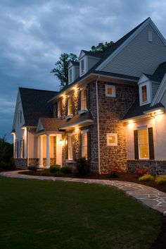 Model home with stone veneer, exterior lighting, shutters, 3 dormers, and a flagstone walkway.