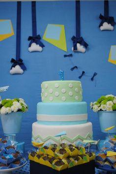 Um bolo simples e lindo em azul e verde para aniversário de menino. O tema escolhido para comemorar o primeiro ano foi brinquedos de menino. Na decoração muitas pipas, cata-ventos, aviões, barquinhos e piões.