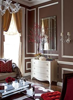 """Designer James Rixner created this Valentine's Day-inspired living room for the Holiday House Designer Showcase. """"My goal was for visitors to experience a grand traditional space in a totally new way,"""" Rixner says. Dark brown walls and champagne-colored draperies are punctuated with passionate red accents. Matching chairs from Century with sexy cushions are covered in tufted cinnabar silk."""