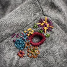 Using colorful embroidery to embellish holes in a sweater. Gorgeous!