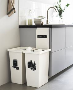 Two large, white bins next to a kitchen counter are labeled for recycling.