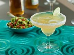 Ultimate Margarita : Recipes : Cooking Channel 1 lime, halved Coarse salt 1/2 cup freshly squeezed lime juice, from about 4 limes 1 tablespoon sugar 1/4 cup orange-flavored liqueur (recommended: Grand Marnier) 1/4 cup Triple Sec 1 cup gold tequila Ice 1/2 can good quality lager-style beer Lime wheels, for garnish