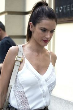Casual chic: The Brazilian beauty showed off her lithe torso in a white halterneck top, which she combined with a cream handbag slung over her right shoulder