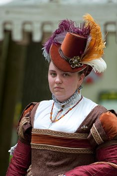 Elizabethan Lady's riding hat. Orange cotton velvet, brown silk trim, brown cording and dyed plumes. 1574 design.    Photo by Mark Meier, http://www.fairephotography.com/index.html    Created by Jamie Butler, http://handmadehistorical.blogspot.com/