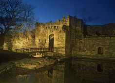 Beaumaris Castle and the water filled moat illuminated at night, Beaumaris, Isle…