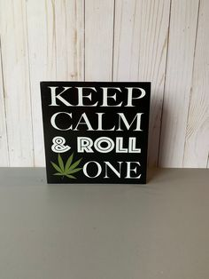 KEEP CALM AND ROLL ONE sign is adorable and trendy for any room in the home. Measures MDF wood sign Hand painted black White and green vinyl lettering Sealant Easy hanging