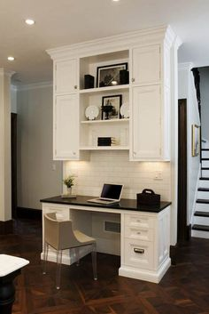 Fabulous kitchen with built-in desk featuring white cabinets accented with polished nickel hardware topped with a sleek black counter alongside a subway tiled backsplash below stacked shelves finished with an acrylic legged chair over parquet wood floors.