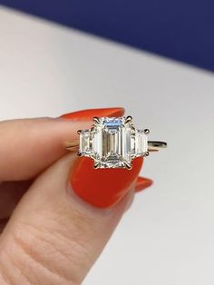 Three stone emerald cut engagement ring in yellow gold with 0.25 carat trapezoid sidestones