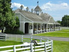 Beautiful single row 8 horse barn in Greenwich CT, the clipped-gabled roofs allude to a Germanic influence, and the soft green helps it blend into the area, while the white trim helps bring in the fencing as a part of the grounds.