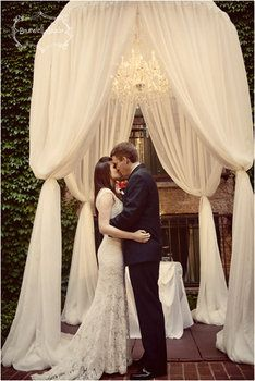Stunningly elegant draped fabric chuppah with tucked legs & chandelier.