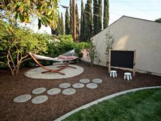 """This """"kids only"""" backyard space features a hammock, hopscotch steps and a pint-sized chalkboard for endless hours of fun. 
