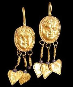A rare and stunning pair of Greco-Roman earrings depicting the face of Eros or Cupid. Pendants of gold hearts and blue glass paste beads complete each piece. 1st century B.C. to 1st. century A.D.