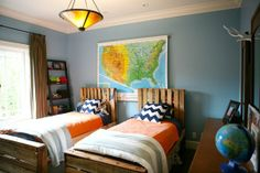 Shared blue boy's bedroom with large map hanging and pallet beds.