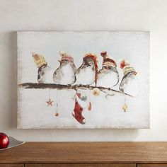 The holidays are better when celebrated together. Our adorable Christmas bird art is a whimsical reminder of that. Five plump little birds in their winter hats perch on a festive branch decorated for the season.