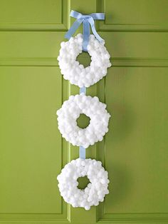 DIY Snowball Wreath --   Hot-glue fuzzy white pom-poms over three small foam wreaths, overlapping the pom-poms to fill in any gaps. Cut a length of ribbon and hot-glue the wreaths to the ribbon. Tie extra ribbon into a simple bow and hot-glue it in place at the top.   Tip: Look at the wreaths from all angles to make sure you have completely covered the foam bases.