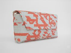 "This envelope clutch is hand-woven with natural cotton yarn and recycled plastic bags from Home Depot.  The plastic has been cut and woven in a technique so that the color and printed graphics create a modern, abstract, bold appearance. A perfect color for a summer accessory.        Fully lined with inside zipper pocket      Magnetic flap keeps bag securely closed      Detachable 48"" cross body strap      Dimensions: 13"" x 5.5"" x 1.5"""