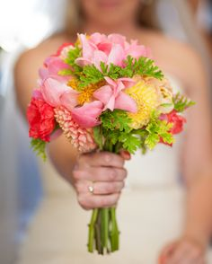beautiful peony, dahlia and poppy bouquet with bright pinks. fresh greens, and citrus yellow & orange