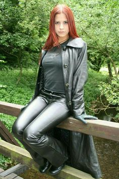 Redhead amateur in leather pants and leather trench coat seated on bridge