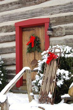 Sweet rustic red door on the mountain cabin. Lovely winter scene.