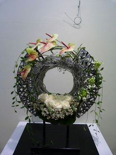 Wonderful piece of floral art using anthuriums and roses. I love circular pieces!