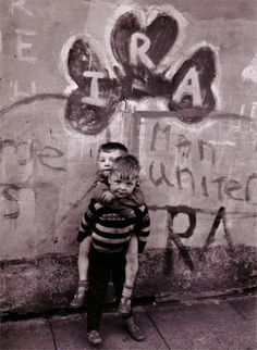 Children play beneath IRA graffiti.
