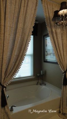 Use a tension rod to hang a curtain over the bathtub (this is an old bedspread repurposed as curtain panels). | 11 Magnolia Lane