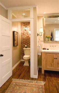 Toilet closet with wood floors, brick wall and transom window #master bathroom ideas