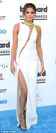 On off love: Selena certainly dressed to kill for the event, she wore a white dressed trimmed with neon flashes with a slashed sheer panel at the front
