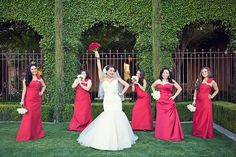 Long red one strap bridesmaid dresses with white bouquets while bride had her wedding dress and a red bouquet | villasiena.cc