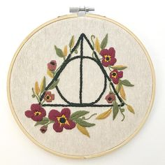 The Sign of the Deathly Hallows, representing the elder wand, resurrection stone, and cloak of invisibility, is an iconic symbol from the Harry Potter series. In this handmade piece of embroidery art Ive entwined the Hallows symbol with Gryffindor-themed flowers. This piece is