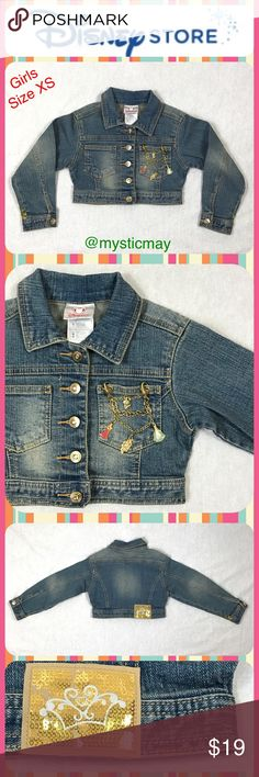 """Girls DISNEY Princess Cropped Denim Jean Jacket 3T Adorable cropped jean jacket from the Disney Store for your little princess! This jacket has rhinestone accented buttons down the front and a gold-tone detachable Princesses charm bracelet detail on the front pocket. Girls Size XS or 4. Measures 13"""" across the chest and 10"""" in length. Sleeves are 14"""" long and can be unbuttoned and cuffed. New, Never Worn but I did notice some sequins were missing on the back patch. Disney Jackets & Coats…"""