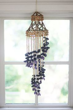 A stunning macrame hanging made entirely of shells. Gorgeous cascading at bottom, finished off with striking blue and purple shells. An incredible statement piece for any home or party.    One small strand of shells appears to be missing, but its hardly noticeable and does not take away from the beauty of the piece whatsoever.    Length: 25 inches including hanger at top  Maximum diameter: 5.5 inches