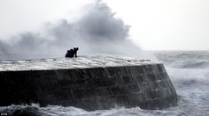 Trying to get a better view:People watch as waves crash over the Cobb at Lyme Regis, Dorset, as Storm Frank begins to batter the UK on its way towards flood-hit areas. The country is set to bring misery to western coasts but also flood-hit communities in the north of Britain