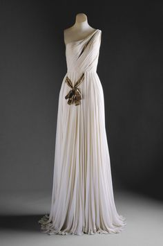 """Designer: Madame Grès Date: fall/winter 1954–55 Culture: French Medium: silk Accession Number: C.I.56.60.6a, b This dress from Madame Gres is very reminiscent of the chitons that they used to wear in ancient Greek. However, it is given a """"modern"""" update with the asymmetrical silhouette and beautiful pleats that run throughout the body. Furthermore, a gold lame ribbon juxtaposes the diagonal pleats of the torso with the straight pleats of the skirt."""