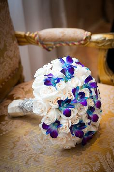 The bride carried a vibrant bouquet of white roses and blue and purple orchids.   	Venue: Leonard's Palazzo  	Flowers / Decor: Stylish Events NY
