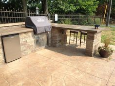 Custom paver grill station with concrete countertop, bar and refrigerator