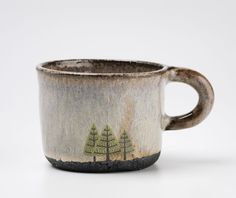 Rustic handmade mug with pine tree design.Thrown and hand modelled with black clay and decorated with food-safe glazes and a hand drawn tree decal.Size: W9cm x H9cmPlease allow 3 weeks for orders to be made. If you looking for something that is ready to post now please have a look at my Etsy and Folksy shops. https://www.etsy.com/shop/JuliaSmithCeramicshttps://folksy.com/shops/juliasmithceramics