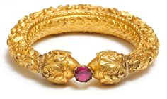 A Large Repousse Gold Bangle Inset With Foiled Fed Stone  Tamil Nadu, South India. 19th Century. 24 carat gold