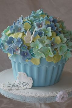 This is a vanilla sponge giant cupcake with vanilla buttercream and raspberry jam. The cake is covered with more than 160 handmade hydrangea blossoms and it all sits nicley on a fondant covered board with a scalloped edge and blue lace. Deco Cupcake, Giant Cupcake Cakes, Large Cupcake, Small Cake, Cupcake Ideas, Pretty Cakes, Beautiful Cakes, Amazing Cakes, Cupcakes Design