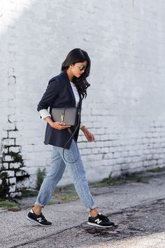 A navy blazer with distressed jeans, a crossbody bag, and sneakers