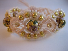 """This unique bracelet is created with cloisonne, crystal and seed beads on cream colored cord. It features a button and loop closure, and fits approximately a 7.5"""" wrist comfortably."""
