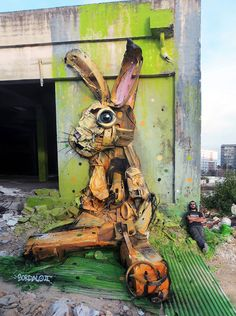 Portuguese street artist Bordalo II (also known as Arturo Bordalo) takes crumpled bumpers, scorched garbage cans and old rubber tires and transforms them into 3-D mural portraits of animals, like the rabbit above.