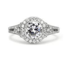The antique center diamond in this ring features beautifully handfaceted work for a unique look. ?The rings cathedral setting is encrusted with filigree work and pave diamonds.
